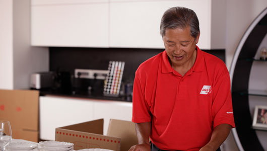 AGS Movers staff member busy packing items into boxes for moving.