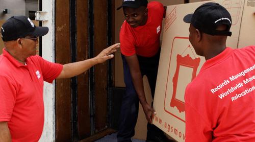 Men loading a truck with a big carton