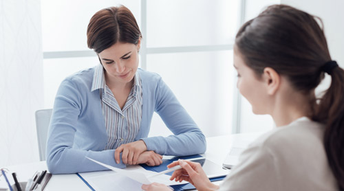 Two women meeting and filling a contract